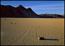 Tracks, moving stone on Racetrack playa and Ubehebe Peak, late afternoon. Death Valley National Park, California, USA. (color)