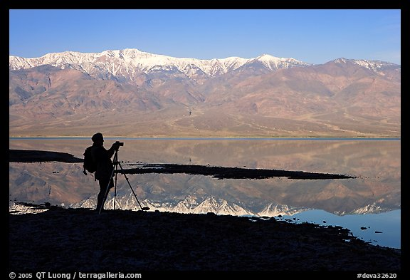 Photographer and Panamint range reflected in a seasonal lake, early morning. Death Valley National Park (color)