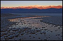 Salt pool and sunrise over the Panamints. Death Valley National Park, California, USA.