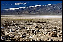 Rock field, salt flats, and Panamint Range, morning. Death Valley National Park, California, USA.