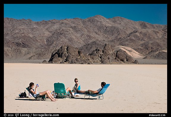 Tourists sunning themselves with beach chairs on the Racetrack. Death Valley National Park (color)