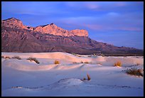 White gyspum sand dunes and cliffs of Guadalupe range at dusk. Guadalupe Mountains National Park, Texas, USA.