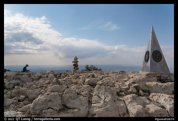 Hiker sitting on Guadalupe Peak summit with cairn and monument. Guadalupe Mountains National Park (color)