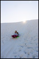 Woman sledding down dune. White Sands National Park ( color)