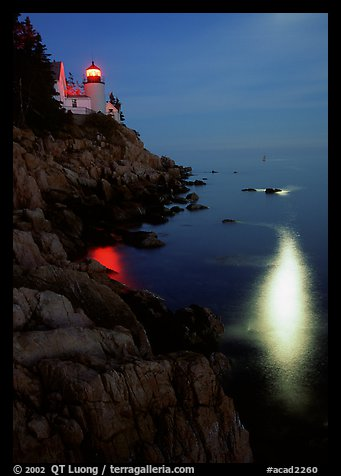 Bass Harbor lighthouse by night with reflections of moon and lighthouse light. Acadia National Park (color)