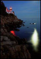 Bass Harbor lighthouse by night with reflections of moon and lighthouse light. Acadia National Park, Maine, USA.