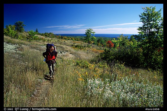 Backpacker walking on Greenstone ridge trail. Isle Royale National Park (color)