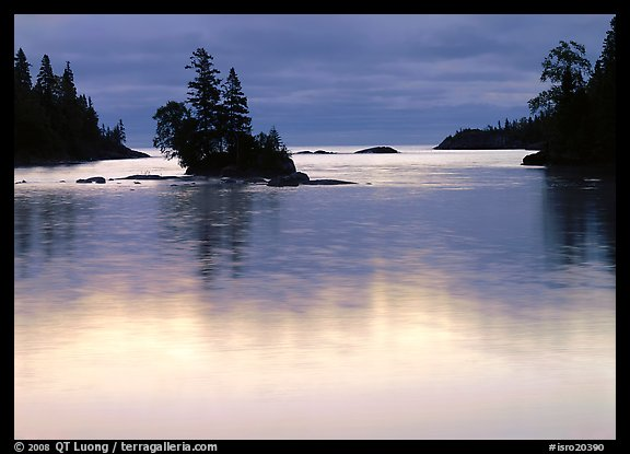 Islet and bright sky reflected in water below dark clouds. Isle Royale National Park (color)