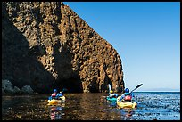 Kayakers paddling in kelp at base of sea cliff, Santa Cruz Island. Channel Islands National Park ( color)