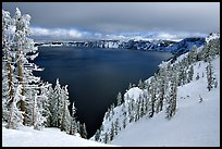Trees and lake in winter with clouds and dark waters. Crater Lake National Park, Oregon, USA.