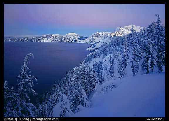 Snow-covered rim and trees, lake and mountains, dusk. Crater Lake National Park (color)