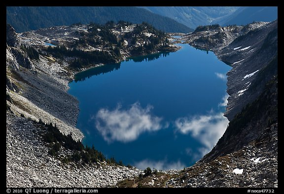 Fluffy clouds reflected in blue lake, North Cascades National Park.  (color)
