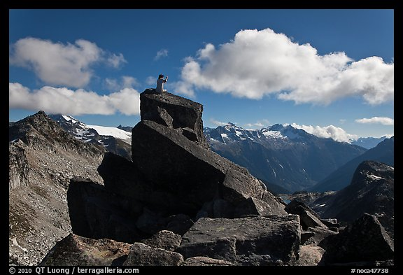 Man sitting on rock photographs mountain panorama, North Cascades National Park.  (color)