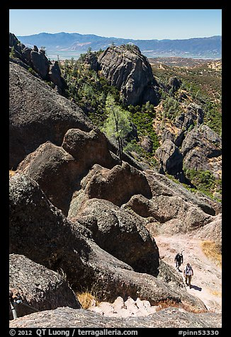 Hikers approaching cliff with steps carved in stone. Pinnacles National Park (color)