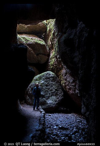 Hiker with headlamp in Bear Gulch Cave. Pinnacles National Park (color)