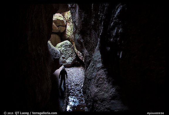 Hiker with lamp in Bear Gulch Cave. Pinnacles National Park (color)