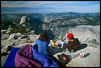 Backpackers eat breakfast, looking at Yosemite Valley from Clouds Rest. Yosemite National Park, California, USA. (color)