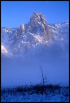 Sentinel Rock rises above the fog of the Valley floor in winter. Yosemite National Park, California, USA.