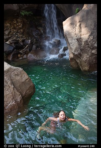 Girl swims in cool pool at the base of Wapama falls. Yosemite National Park (color)