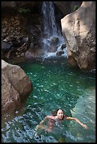 Girl swims in cool pool at the base of Wapama falls. Yosemite National Park, California, USA.
