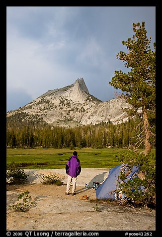 Camper standing next to tent looks at Cathedral Peak, evening. Yosemite National Park (color)