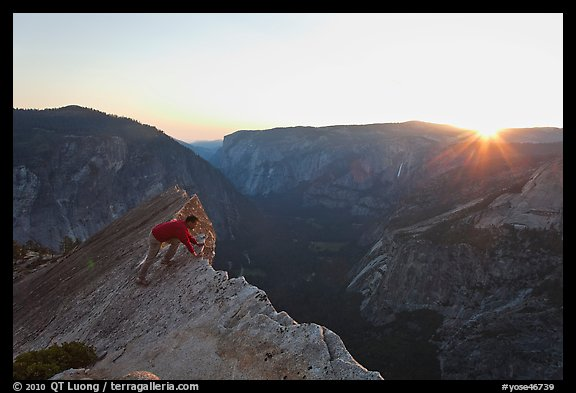 Hiker looking over the edge of the Diving Board, sunset. Yosemite National Park (color)