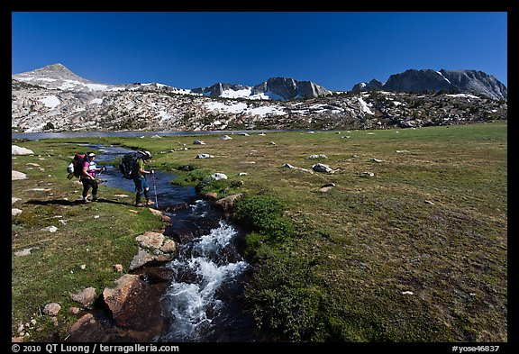 Backpackers crossing stream, Evelyn Lake. Yosemite National Park (color)