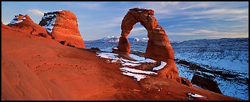 Desert Arch and mountains at sunset. Arches National Park (Panoramic color)