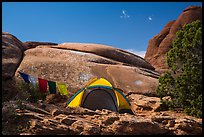 Tent with prayer flags amongst sandstone rocks. Arches National Park, Utah, USA. (color)