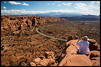 Tourist taking picture from top of fin. Arches National Park, Utah, USA.