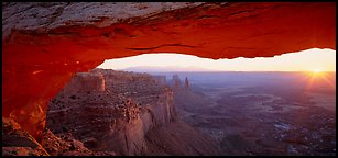 Sunrise and canyon landscape through Mesa Arch. Canyonlands National Park (Panoramic color)