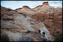 Hikers climbing out of High Spur slot canyon, Orange Cliffs Unit, Glen Canyon National Recreation Area, Utah. USA (color)