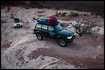 4WD vehicles driving over rock at dusk in Teapot Canyon. Canyonlands National Park, Utah, USA.