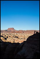 Hiker standing in silhouette above the Maze. Canyonlands National Park, Utah, USA. (color)