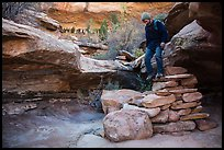 Hiker stepping down on primitive stairs, Maze District. Canyonlands National Park, Utah, USA. (color)