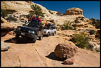 Vehicles on ledge in Teapot Canyon. Canyonlands National Park, Utah, USA. (color)