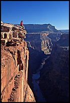Visitor sitting on  edge of  Grand Canyon, Toroweap. Grand Canyon National Park, Arizona, USA. (color)