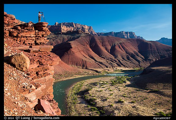 Photographer on steep cliff above Unkar rapids. Grand Canyon National Park (color)