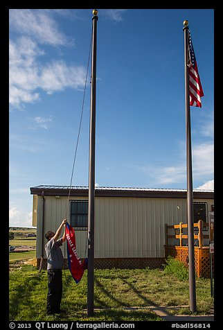 Ranger lowering Ogala Lakota flag, White River Visitor Center. Badlands National Park (color)