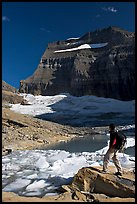 Hiker with backpack surveying Grinnell Glacier. Glacier National Park, Montana, USA.