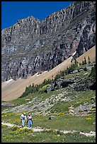 Couple hiking on trail amongst wildflowers near Hidden Lake. Glacier National Park, Montana, USA.