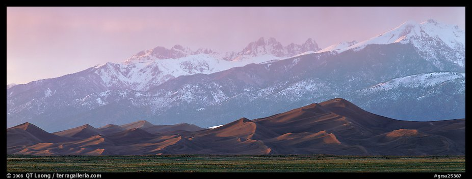 Sand dunes below snowy mountain range at sunset. Great Sand Dunes National Park and Preserve (color)