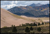 Sangre de Cristo range with bright patches of aspen above dunes. Great Sand Dunes National Park, Colorado, USA. (color)
