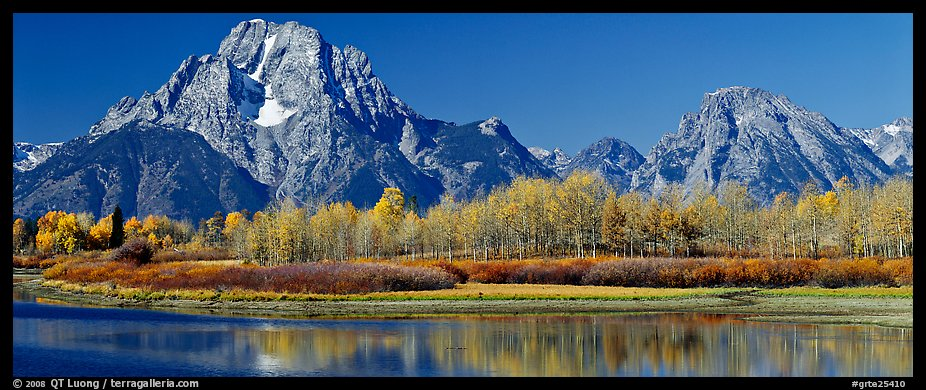 Rugged mountains rising above tree-lined lake in autumn. Grand Teton National Park (color)
