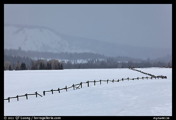 Wooden fence, snow-covered flat, hills in winter. Grand Teton National Park (color)
