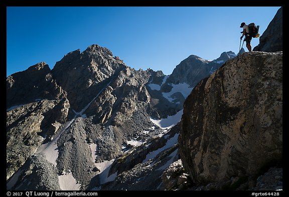 Mountaineer stands on rock looking at peaks, Garnet Canyon. Grand Teton National Park (color)