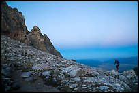 Mountaineer jumps on boulder at Lower Saddle,dusk. Grand Teton National Park ( color)