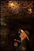 Ranger pointing flashlight at boxwork. Wind Cave National Park ( color)