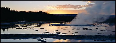 Steam rising in geyser pool at sunset. Yellowstone National Park (Panoramic color)