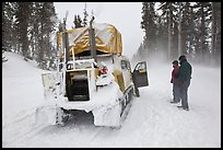 Couple standing in snowdrift next to snow coach. Yellowstone National Park, Wyoming, USA. (color)